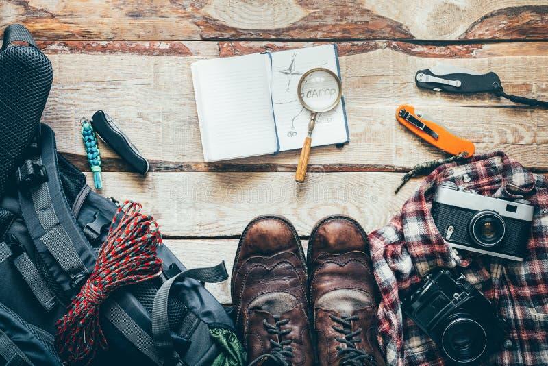 Аксессуары перемещения пешие на старом деревянном столе, взгляд сверху Приключение отдыхает концепция путешествием внешняя стоковое изображение rf
