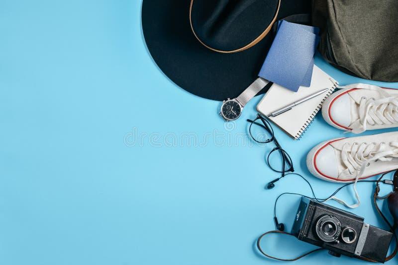 Аксессуары путешественника на голубой предпосылке с ретро камерой, шляпой, рюкзаком, eyeglasses, часами, ручкой, паспортом, ботин стоковое фото