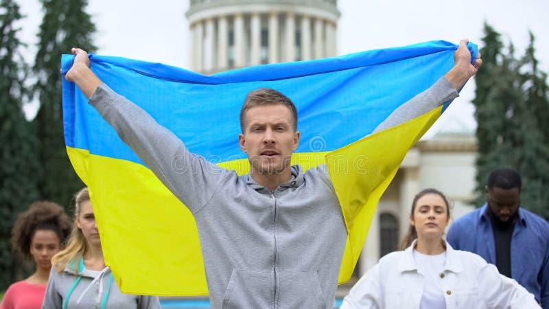 Активисты поднимают украинский флаг, скандируя лозунг, митинг за независимость, патриотизм стоковое фото rf