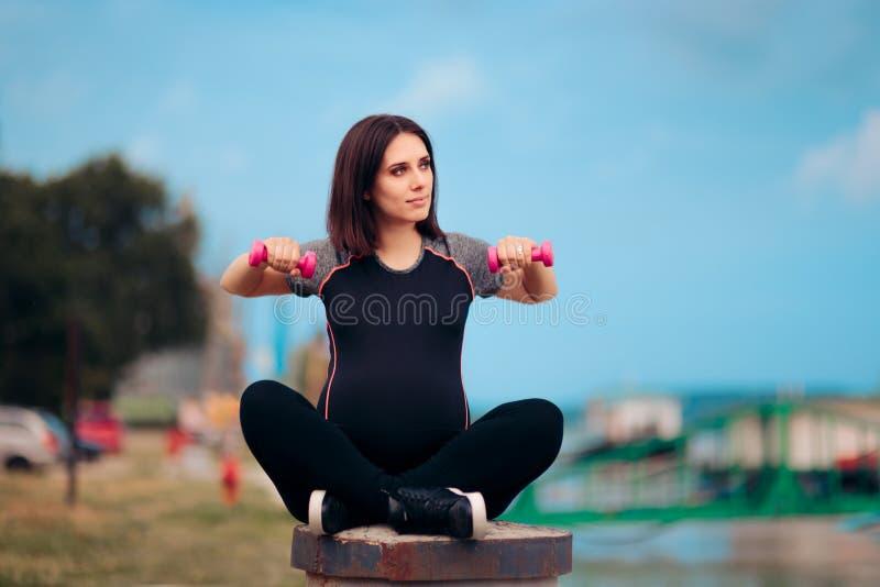 Активная беременная женщина используя гантели Outdoors стоковые изображения