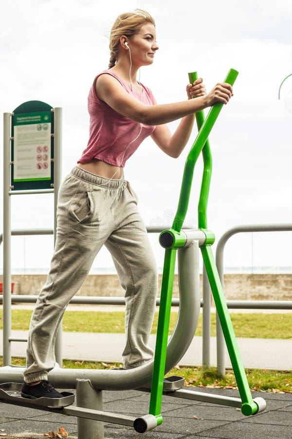 Активная женщина работая на эллиптическом тренере стоковые фотографии rf