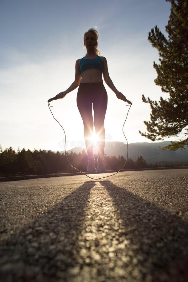 Активная женщина скача с прыгая веревочкой стоковое фото