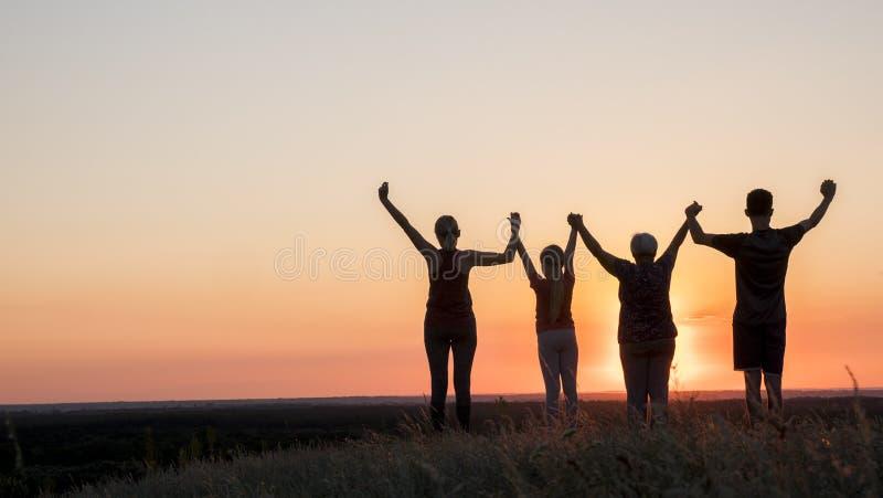 Активная здоровая семья, бабушка с дочерью и внуки встречают рассвет, поднимают их оружия выше стоковые фото