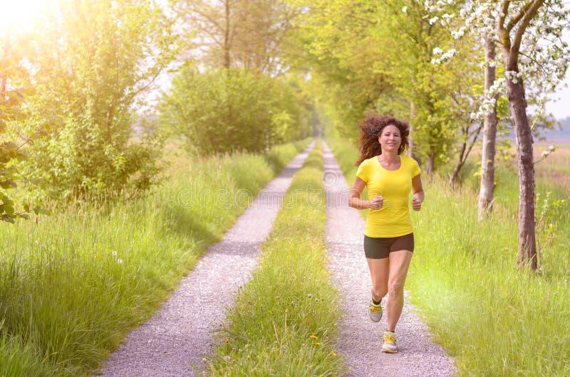 Активная здоровая молодая женщина наслаждаясь бегом утра стоковое изображение