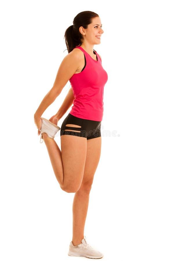 Активная нога простирания молодой женщины изолированная над белой предпосылкой стоковая фотография