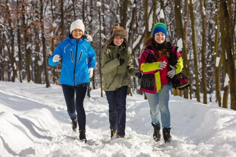 Активная семья - мать и бежать детей внешний в парке зимы стоковое изображение rf