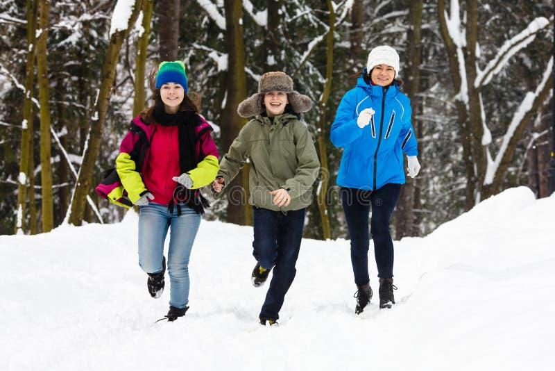 Активная семья - мать и бежать детей напольный в парке зимы стоковые фото