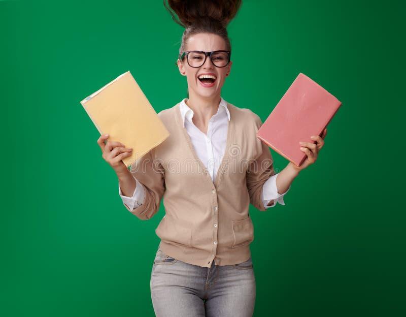 Активная современная женщина студента с книгами на зеленой предпосылке стоковые изображения