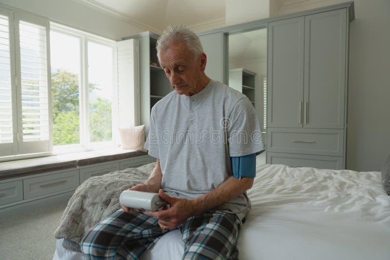Активное кровяное давление старшего человека измеряя со сфигмоманометром в спальне стоковое фото