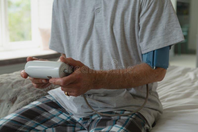 Активное кровяное давление старшего человека измеряя со сфигмоманометром в спальне дома стоковые изображения rf