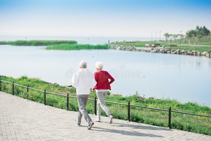 Активные старшие пары бежать вдоль озера стоковая фотография