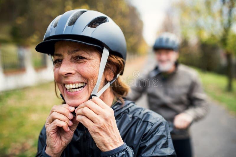 Активные старшие пары с electrobikes стоя outdoors на дороге в природе стоковое фото