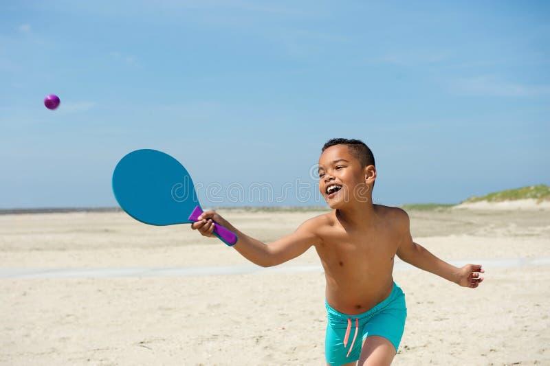 Активный мальчик играя на пляже стоковое фото rf
