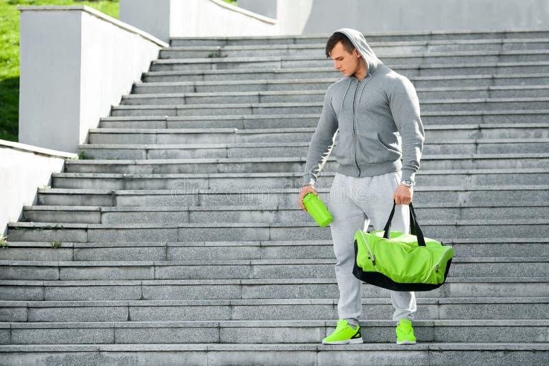 Активный мышечный человек держа шейкер и спорт кладут в мешки, outdoors стоковые изображения rf