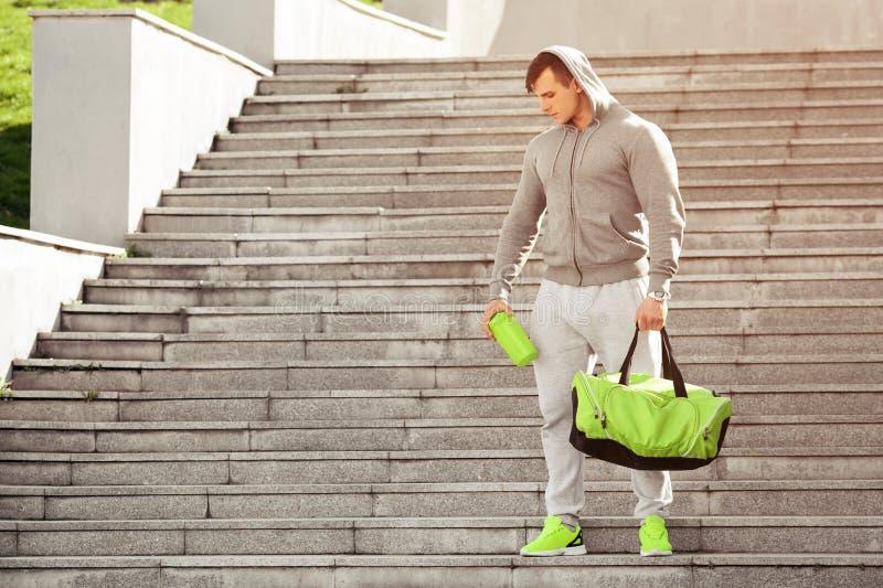 Активный мышечный человек спорта держа шейкер и спорт кладут в мешки, outdoors стоковые изображения