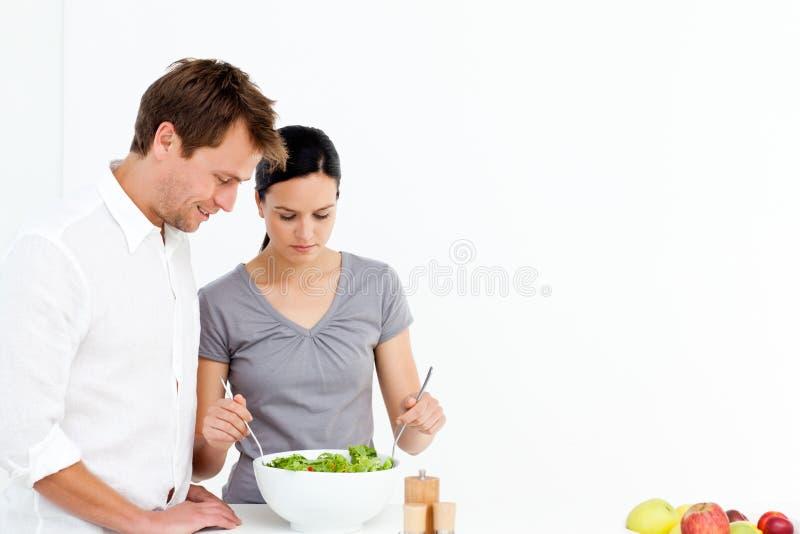 активный обед пар подготовляя салат стоковое фото rf