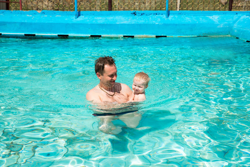 Активный отец уча, что его ребенок поплавал в бассейне на тропическом курорте стоковое изображение rf