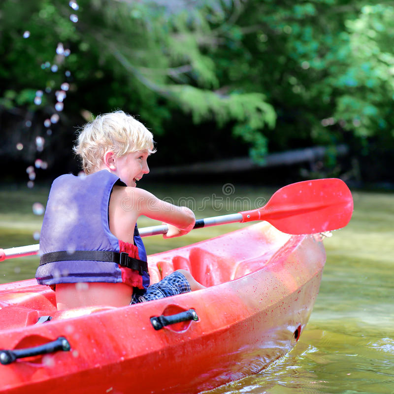 Активный счастливый мальчик сплавляться на реке стоковое изображение