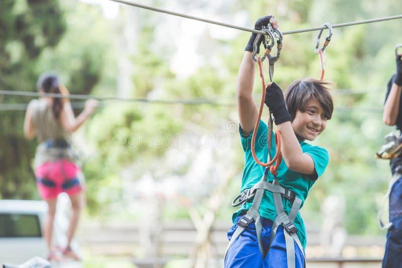 Активный храбрый мальчик наслаждаясь уходящий за границу взбираться на парке приключения дальше стоковое изображение rf
