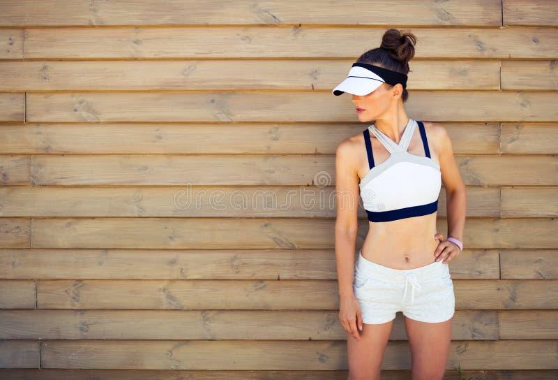 Активный jogger женщины смотря космос экземпляра против деревянной стены стоковое изображение rf