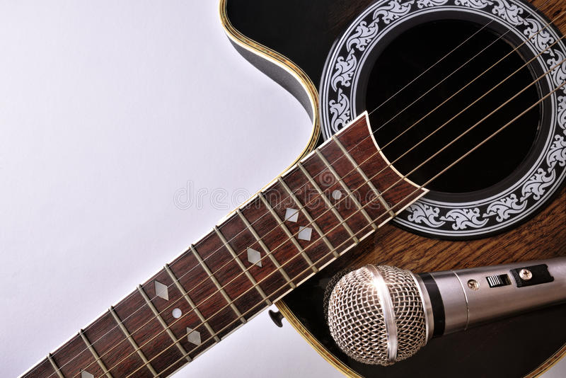 Акустическая гитара и микрофон изолированные на белой столешнице стоковые изображения rf