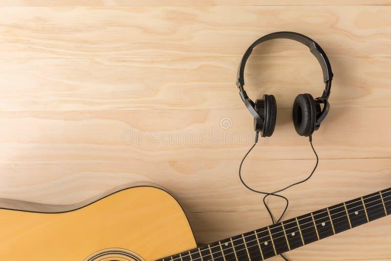 Акустическая гитара и наушники стоковые фото