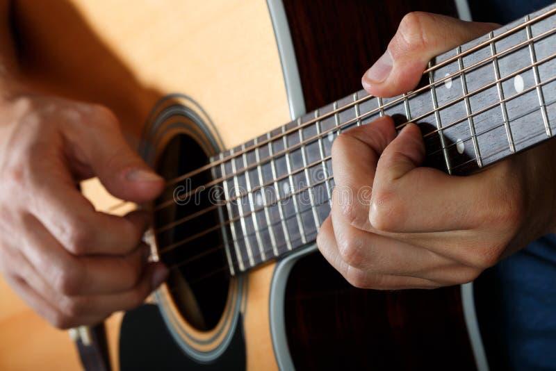 Акустический гитарист выполняя песню стоковая фотография