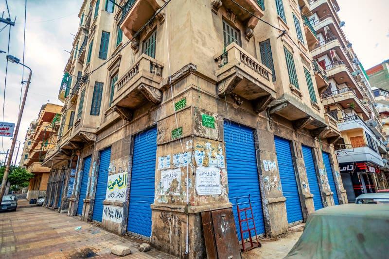 11 16 2018 Александрия, Египет, вид угла старого дома с яркими и голубыми дверями затопленными со старыми рекламами стоковые фото