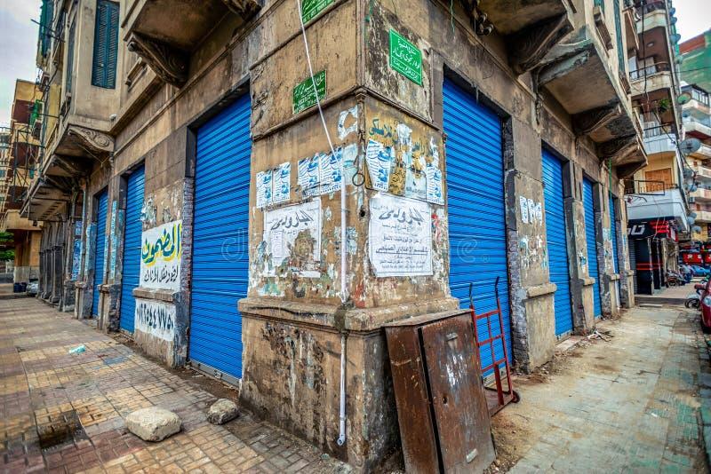 11 16 2018 Александрия, Египет, вид угла старого дома с яркими и голубыми дверями затопленными со старыми рекламами стоковое изображение rf