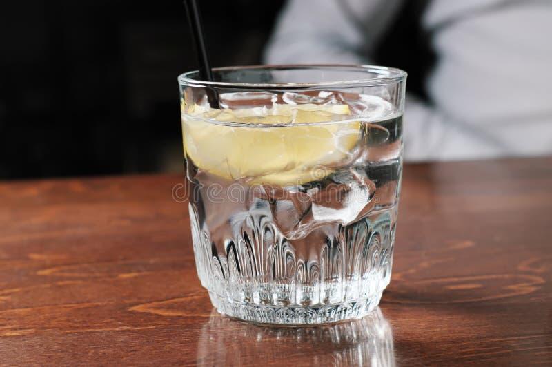 Алкогольный напиток с лимоном и льдом на старом деревянном столе стоковые фотографии rf