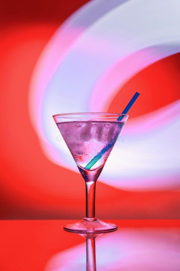 Алкогольный напиток с льдом и соломой в стекле на красной предпосылке стоковое изображение