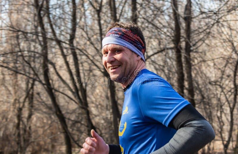 АЛМА-АТА, КАЗАХСТАН - 16-ое марта 2019: портрет красивого зрелого неопознанного человека которого бежит через древесины во время стоковые изображения rf