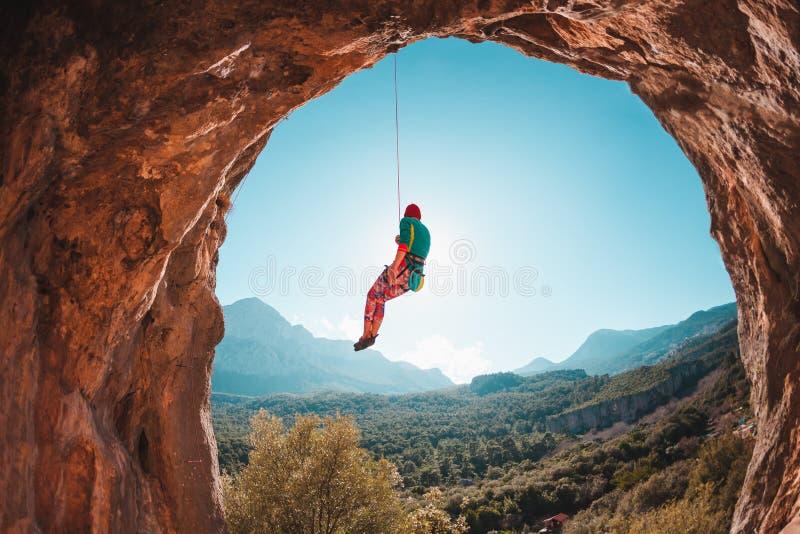 Альпинист висит на веревочке стоковые фото
