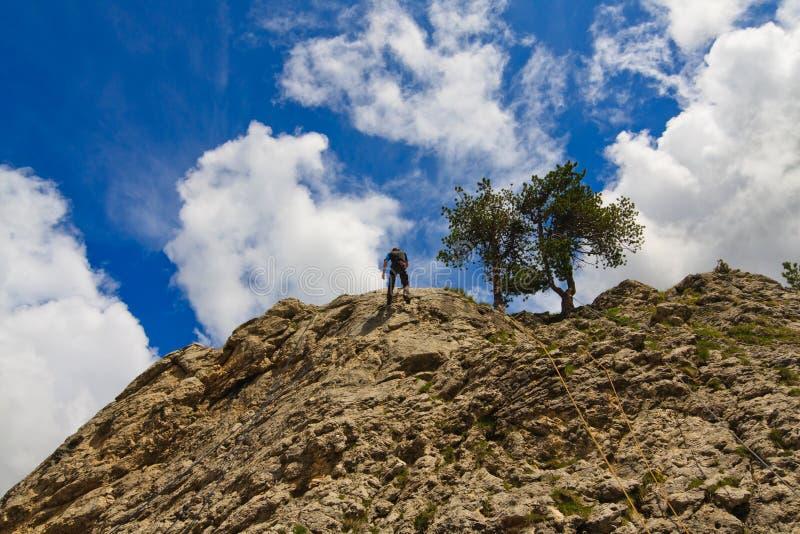 альпинист вниз выравнивает утес сползая использующ стоковое фото rf