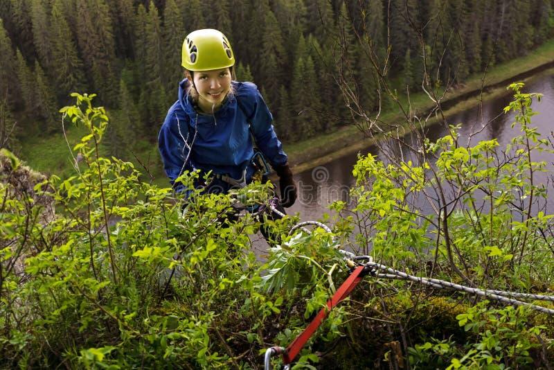 Альпинист девушки начинает спуск от скалы стоковые изображения