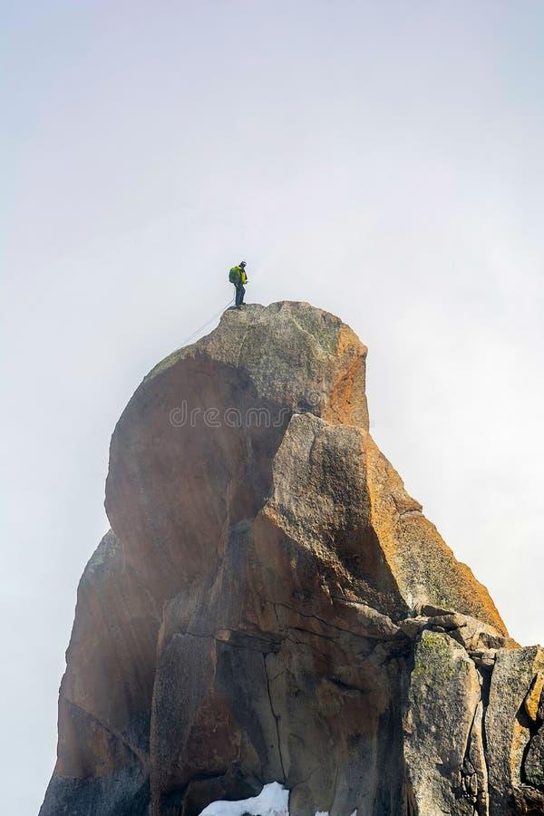 Альпинист достигая саммит стоковое фото