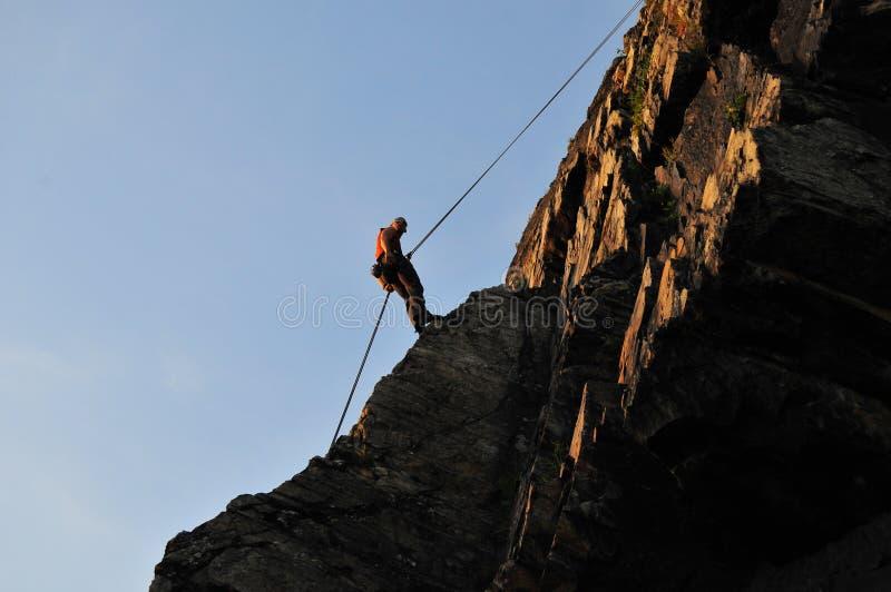 альпинист отталкивая утесом стоковое фото