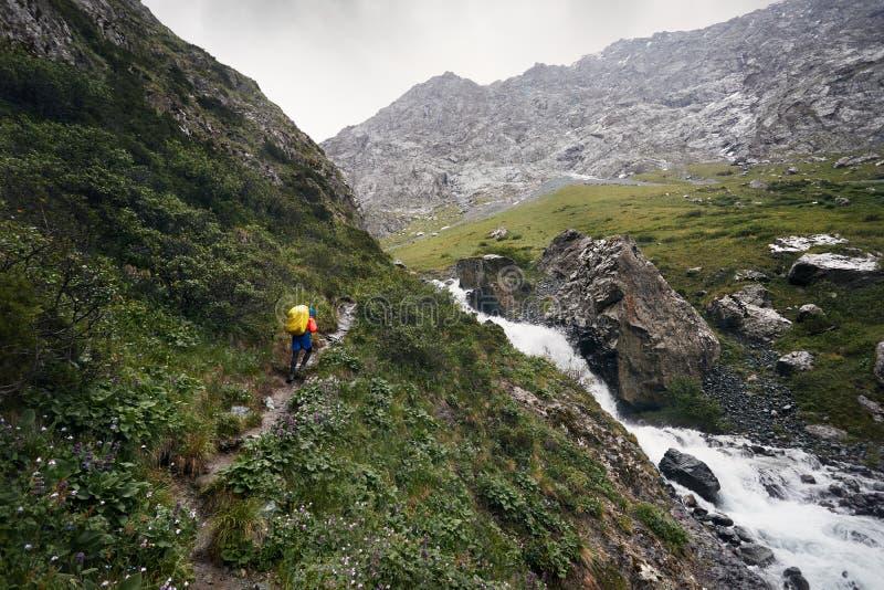 Альпинист с рюкзаком в горах стоковое изображение rf