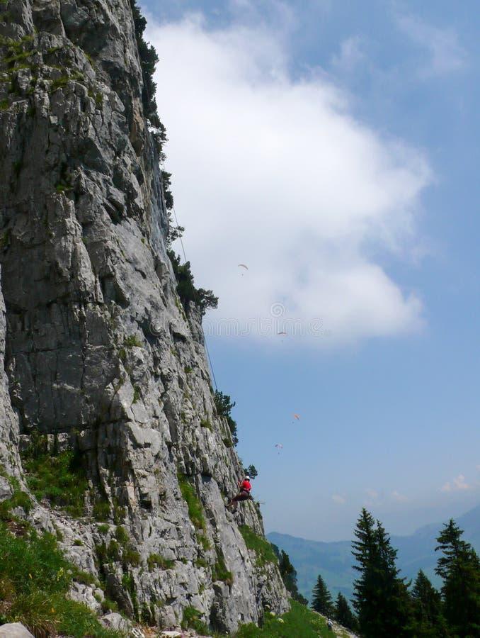 Альпинист утеса rappelling с крутой стороны горы утеса на безопасную землю с летанием параплана в голубом небе позади стоковая фотография