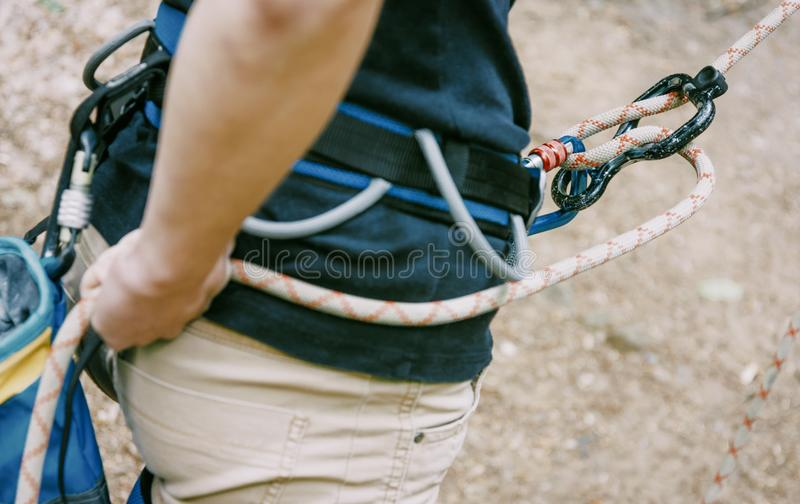 Альпинист belaying с веревочкой и диаграммой 8 на открытом воздухе стоковая фотография rf