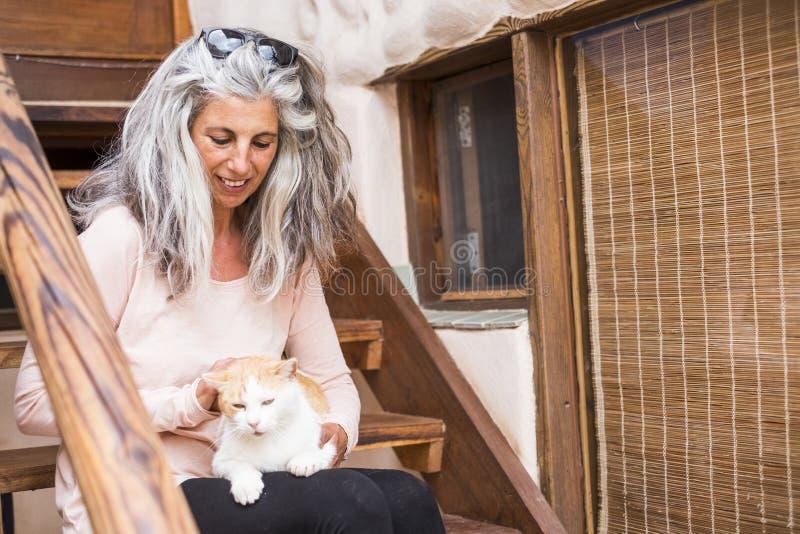 Альтернативный кавказский средний возраст женщины с длинными серыми и белыми волосами позаботится о кот на ее ногах сидит вниз на стоковое фото