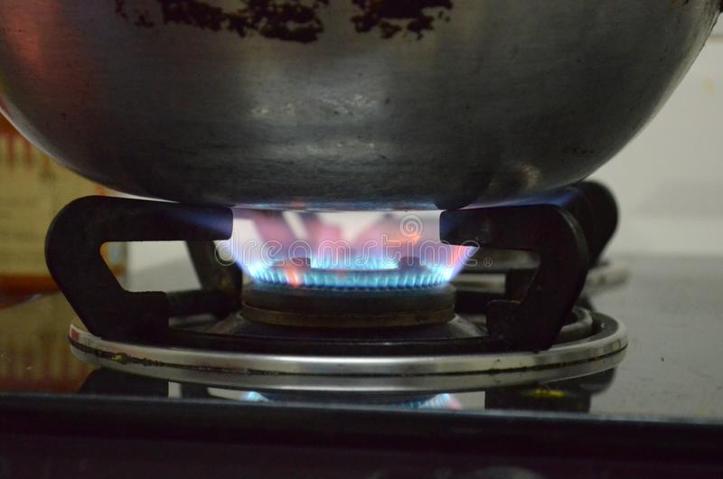 Алюминиевый лоток под пламенами в газовой плите; варить старого стиля стоковая фотография