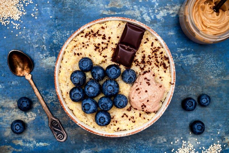 Амарант клейковины свободные и шар завтрака каши квиноа с голубиками и шоколадом над деревенской деревянной предпосылкой стоковая фотография rf