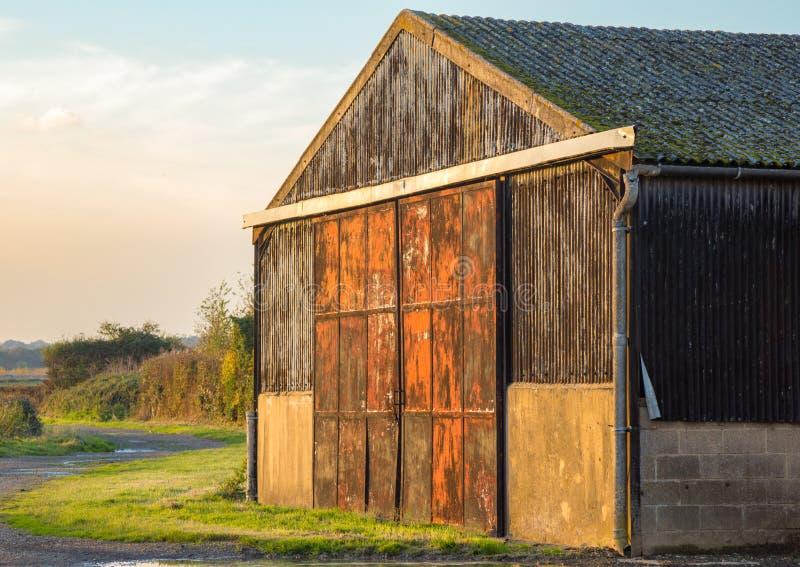 Амбар на обрабатываемой земле с дверями металла красными и ржавыми стоковое изображение