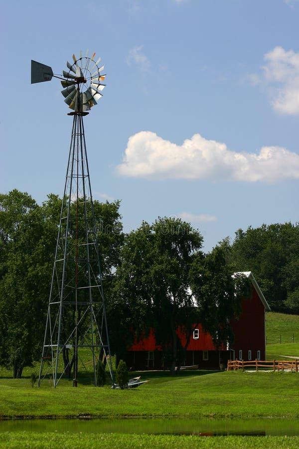 амбар под голубыми облаками field пушистая зеленая ветрянка белизны валов неба стоковые фото