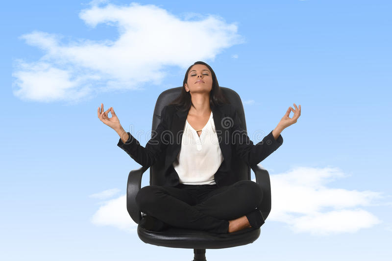 Американская бизнес-леди сидя на стуле офиса в йоге и раздумье позиции лотоса практикуя стоковое фото rf