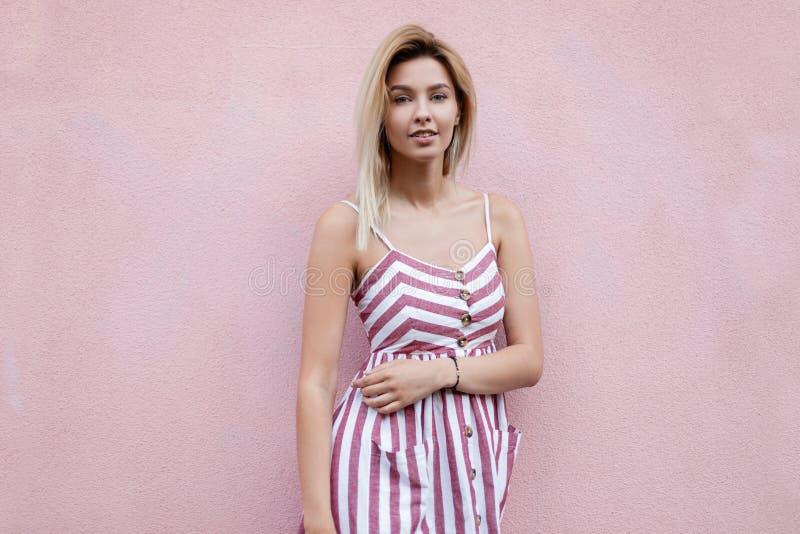 Американская блестящая молодая женщина со светлыми волосами в стильном striped розовом платье представляя положение около розовог стоковое фото rf