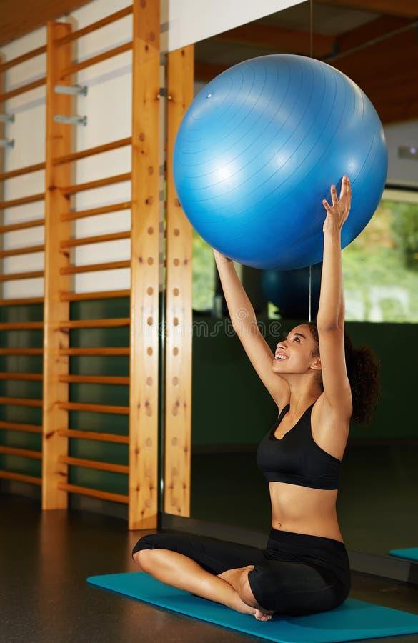 Американская женщина держа шарик Pilates смотря настолько счастливый стоковая фотография