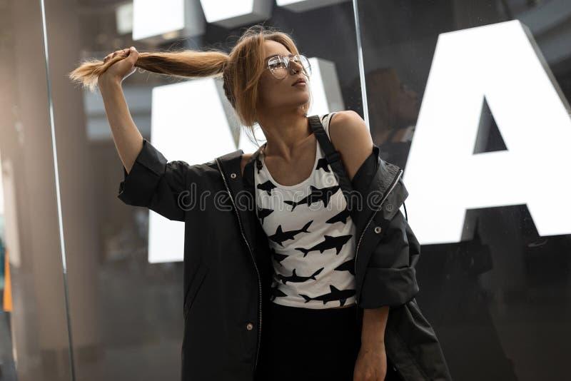 Американская милая молодая женщина в винтажных стеклах в модном плаще в стильной белой футболке с представлениями картины внутри  стоковое фото
