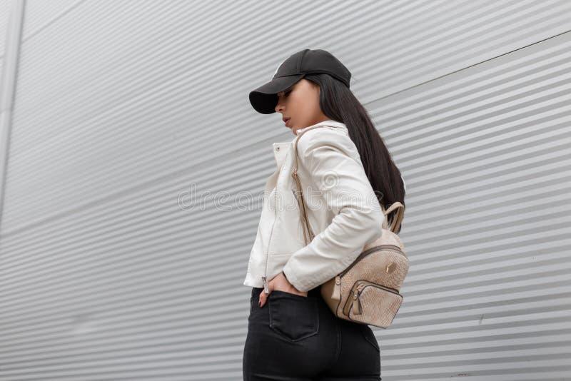 Американская молодая женщина в стильной крышке с ультрамодным рюкзаком золота в винтажной белой кожаной куртке путешествуя вдоль  стоковые фото